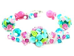 GlassRiverJewelry: Handmade lampwork bracelet featuring SRA artisan crafted teal, bright pink, fuchsia and lime green floral lampwork beads; Blue Zircon AB, Fuchsia AB and Rose AB Swarovski crystals; and sterling silver.