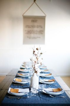 Cozy table scape with cotton branch center pieces and deep blue linens