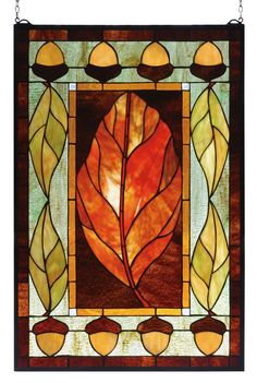 This hand crafted Meyda Tiffany original earth toned stained glass window features a Russet Leaf surrounded by Honey Gold, Rich Browns and Verdant Grass Green with nature inspired acorn and leaves bor