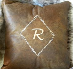 Get the Pablo Cattle Brand inside. Custom Decorative Throw Pillow Embroidered with Initial Surrounded by a Frame of Barb Wire on micro suede leather.
