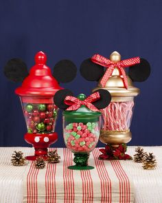 "Make Mickey and Minnie the center of your holiday table by adding the iconic ears and a little Christmas décor to simple pedestal jars. Fill them with candy so they become a sweet treat for your friends and family. Get guests involved at your next holiday party by using your centerpiece as a fun ""guess how many candies are in the jar"" game."