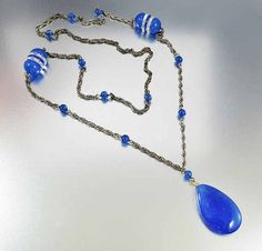 A blue hand blown glass pendant sways from a silver French rope chain in this circa 1930s Art Deco necklace. Punctuated through the chain are blue chalcedony beads along with faceted crystal rounds. Take a trip back in time with this lovely bauble!  Materials: Silver Gemstone: Glass Measurements: 30 inches long with the pendant measuring 2 inches. Condition: Very good with some wear to the chain and a tiny flake at the very top of the pendant  More vintage necklaces can be found here……