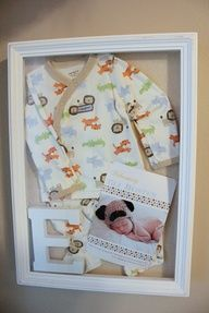 Frame your babys first outfit, initial and birth announcement in a shadow box.  Use white pearl straight pins to keep the outfit and announcement in place the way you want them and then just placed the initial in the corner and shut the door.  Voi La!