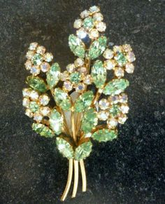 This is a pretty vintage floral spray brooch.  Studded with green and clear aurora borealis  rhinestones.  The rhinestones are set against a gold tone metal.  Vintage circa 1960's - 70's.