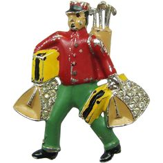 An Art Deco rhodium plated and multiple color enameled resort bellhop brooch with golf clubs, the detailed and obviously high end version of this popular collectible is in very good condition, you can count all 5 fingers clutching both bag handles and see the sleeve of his jacket is corded with the shirt just peeking out from under it …. an amazing find from brendastreasures on rubylane.com!