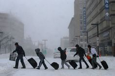 Travelers leave Back Bay train and subway station during winter nor'easter snow storm in Boston