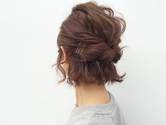 Short curly hair in a half-up, pinned back style.