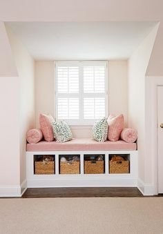 Pink girl's room features a nook filled with a built-in window seat fitted with open cubbies filled with woven baskets topped with a dusty pink linen cushion with white piping as well as matching bolster pillows, pink zigzag pillows in Quadrille Fabrics Petite Zig Zag and dalmatian print pillows in Thibaut Tanzania Fabric.