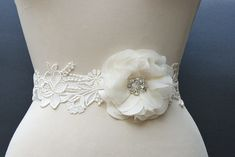 cute belt idea. blue aplique lace and floofy flower either ivory or blue (or purple)
