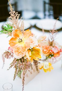 Love the looseness of these orange and pink centerpieces | Photo by Nancy Neil