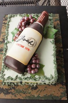 Red wine bottle on green sheet cake with grapes