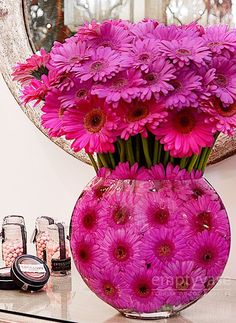 """Sweet Pink Daisies by Empty Vase Florist   A Vibrant mix of Gerbera Daisies in different shades of pink are masterfully arranged in a 10"""" tall flat fish bowl lined with more blooms of the flower. This arrangement is approx. 21""""-23"""" tall."""