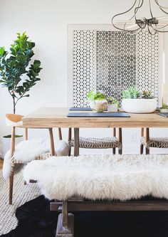 A bohemian dining space with sheepskin rug on bench, indoor plant in corner, and lots of centerpieces