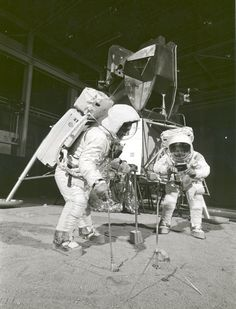 Apollo 11 astronauts simulate gathering soil samples with tongs and scoop in 1969. Neil Armstrong holds the sample bag for Buzz Aldrin with a Lunar Module mockup behind them.