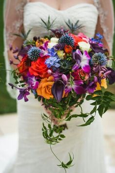 Awesome Jewel Toned Bridal Bouquet Comprised Of: Red, Orange, & Yellow Roses, Red/Yellow Bi-Color Circus Roses, Ivory Roses, Deep Purple Callas, Blue Delphinium, Craspedia, Snow Bells, Blue Eryngium Thistle, Fuchsia/White Orchids, & Green Foliage××××