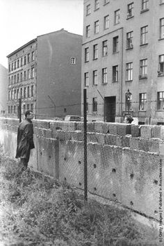 A citizen of East Berlin peers through barbed wire at a West Berliner over the Berlin Wall, Berlin, Germany, 1960s. The mass immigration of Germans from Communist Berlin to Western Berlin inspired East Germany military leader Erich Honeker to construct the blockade, a barricade of concrete walls, mine fields and guard posts that stretched for 100 miles. (Photo by Hulton Archive/Getty Images)