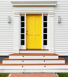 Hello, sunshine! Bold yellow door on a white house makes a great modern statement. I like how the yellow door's vertical lines contrast with the horizontal lines of the steps and siding. Both aspects emphasize each other.
