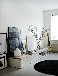 meuble tv bas et blanc de style scandinave, décoré de collages et tableaux