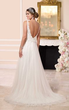 This tulle sheath beach wedding dress from the Stella York wedding dress collection features stunning lace detailing on its bodice, a low back, a court train, and a figure flattering ribbon waist sash.