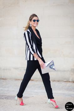 striped top with black pants and statement heels and metallic clutch