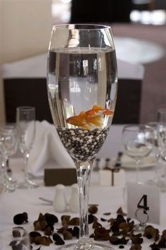 champagne glass fish centerpiece -- Answer: How do you get your party guests to drink fish? Non Floral Centerpieces, Wedding Table Centerpieces, Wedding Flower Arrangements, Wedding Decorations, Glass Centerpieces, Masculine Centerpieces, White Centerpiece, Centerpiece Ideas, Wedding Reception