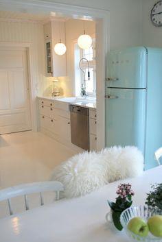 A very crisp, clean, minimalist white kitchen, with powder blue Smeg refrigerator <3