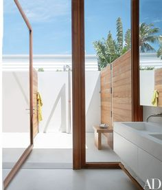In the master bath, the double sink is of Corian; the teak-framed glass doors lead to an outdoor shower | archdigest.com