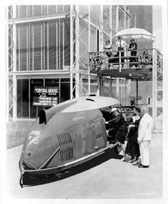 """Buckminster Fuller with Dymaxion Car #3 in front of George F. Keck's """"Crystal House"""" Chicago World's Fair 1933"""