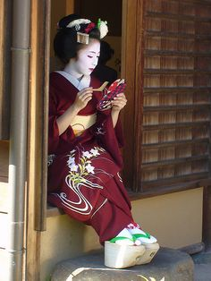 Maiko touching up her makeup. I like how she has her okobo out.