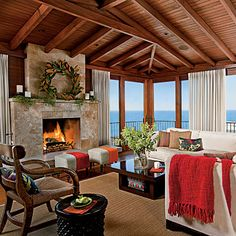 Adore this living room by the beach. The fireplace is beautiful in stone, the beam ceiling totally makes the room and keeps is cozy, along with the red accents.     LOVE OF THE SEA