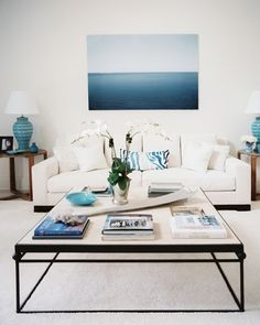 Amazing 37 Sea and Beach Inspired Living Rooms: 37 Sea and Beach Inspired Living Rooms with white blue wall color and sofa pillow table lamp glass table flower decor carpet and hardwood floor – Momtoob