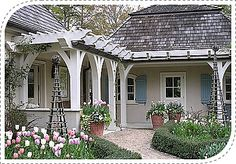 This beautiful pergola would be right at home next to a Cape Cod-style home. Just love the color of the spring tulips. . . Design by AHBL in Washington.