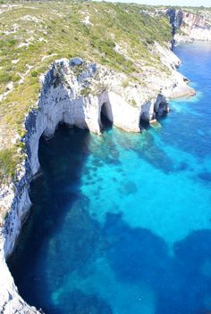 """Zante's """"Blue Caves"""" """"In Zante Island of Greece you can find the interesting sight of Numerous """"Blue Caves"""", that are cut into cliffs around Cape Skinari, and accessible only by small boats. Sunrays reflect through Ionian sea water from white stones of cave bottoms and walls, creating interesting blue effects, thus known as 'Blue Caves'."""""""