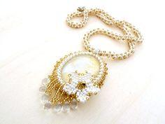 Zlatý+květ+Náhrdelník+vytvořený+technikou+šitého+šperku+z+korálků.+Náhrdelník+je+vytvořen+z+obšitého+skleněného,+ručně+malovaného+kabošonu+z+dílny+malované+kabošony,+ve+zlato-stříbrné-bílé+barvě.+Kabošon+je+obšit+kvalitním+japonským+TOHO+rokajlem+v+bílébarvě+s+lesklouúpravou+a+zlaté+barvě+sestříbrným+průtahem.+Zdobení+kabošonu+je+tvořeno...