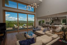 A midcentury style living room creates an indoor-outdoor space with wide-open views of lush hills through the large AG Millworks Multi-Slide Patio Door. Photo by Logan Hall