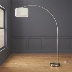 Shop big dipper arc brushed-nickel floor lamp.   A simple brushed round nickel base grounds a wide sweeping arc over six feet high, culminating in a slim ring of cotton/poly with naturally occurring linen slubs.