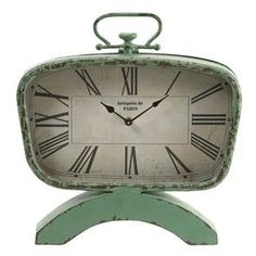 "Midcentury-inspired wrought iron table clock in weathered green with a curved base and Roman numerals.  Product: Table clockConstruction Material: Wrought iron and glassColor: Weathered greenFeatures:   Aged designClassic mid-century shapeStately Roman numerals Accommodates: Batteries - not includedDimensions: 14.5"" H x 13.25"" W x 2.5"" D"