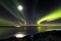 Vlak boven de horizon is nog de staart van de komeet Panstarrs te zien. De IJslandse fotograaf wist deze samen met het noorderlicht, de maan en de sterren vast te leggen. © Ingólfur Bjargmundsson