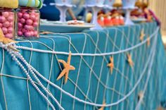"""Blue tablecloth, fishing net, pearls, and starfish are the perfect decor to any table at an """"under the sea"""" themed party - seashells would be awesome as well."""