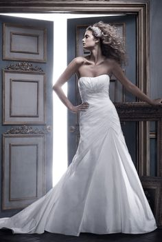 Casablanca Bridal - Camille. Soft sweetheart neckline is accented with rhinestone and pearl applique on bodice. A-line skirt has asymmetrical lattice pleating detail on front and back. The zipper is lined with matching Silk Shantung buttons and loops.