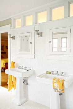 white master bath with double sinks with exposed plumbing, white subway tile, tile floor, built in medicine cabinets, transoms, 1915 crafstman house after remodel