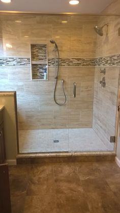 our giant master shower we used natural stone 12x24 size for main shower tile subtle green and beige glass accent tile with a bull nose trim around it