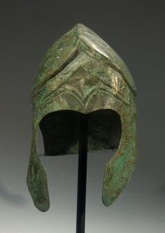 CHALCIDIAN BRONZE HELMET WITH INCISED DECORATION  Narrow elongated skull with a carinated and crested crown, holes for the plume attachment, large cheek pieces, and a short flaring neck guard. The forehead has decorative eyebrows in relief and richly incised palmettes, serpents' heads, locks of hair, and floral ornamentation.  5th-4th Century BC  H. 9 in. (23 cm.)  Ex collection of Axel Guttmann (1944-2001), Berlin, acquired in Krefeld 1990.  Published: J. Eisenberg, Art of the Ancient…