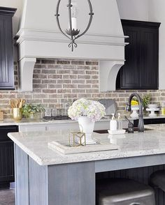Kitchen with black cabinets and large vent hood