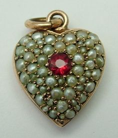 A Victorian c1895 puffy heart charm in, surprisingly, just brass but pave set with real seed pearls and a pink spinel to the centre, polished up to look like rose gold.