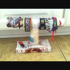Diy braclet holder. Paper towel roll, toliet paper roll, and skinny card board box taped together and covered in magazine pages!!:)