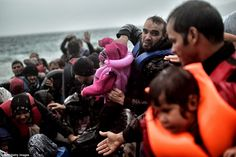 Refugees and migrants scramble onto the shore as they arrive on the Greek Island of Lesbos