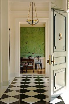elizabeth dinkel entry vignette--black door, black and white checkerboard floor, brass accents, green chinoiserie wallpaper