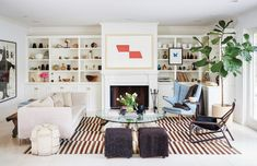 Casual, clean living room with striped rug, white sofa, indoor plant, gray stools, and blue armchair in corner