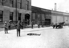 A British Soldier stands by the body of a man killed during the burning of the Custom House in Dublin on 2 May 1921 during the War of Independence. Ireland 1916, Dublin Ireland, Old Pictures, Old Photos, Irish Independence, Dublin House, British Soldier, Revolutionaries, Street View